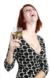 Happy young Woman With A Glass of Wine. Young red head woman in a black and white dress laughs and holds a glass of white zinfandel wine Royalty Free Stock Photo