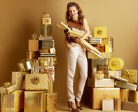 Happy young woman with gold wrapping paper rolls royalty free stock image