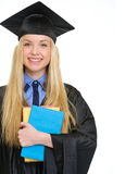 Happy young woman in graduation gown with books Royalty Free Stock Image