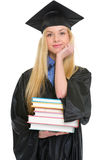 Happy young woman in graduation gown with books Royalty Free Stock Images
