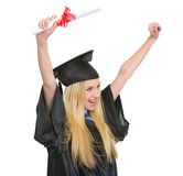 Woman in graduation gown rejoicing success Stock Photos