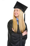 Happy young woman in graduation gown looking on copy space Stock Images