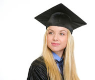 Happy young woman in graduation gown looking on copy space Royalty Free Stock Photos