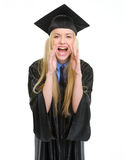 Happy young woman in graduation gown shouting Stock Images