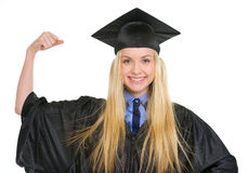 Happy woman in graduation gown showing biceps Stock Photo