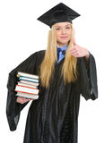 Happy young woman in graduation gown showing books Stock Photo