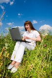 Happy Young Woman on the grass field with a laptop. Smile. In white dress. Computer rests on his knees Stock Photo