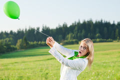 Happy young woman with green balloon meadows Royalty Free Stock Images