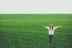 Happy young woman in green field. Happy young woman walking in green field. Pretty girl standing with arms raised in middle of meadow with copy space. Freedom royalty free stock photos