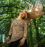 Happy young woman with hair in motion stock photography