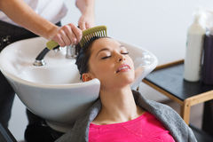 Happy young woman at hair salon. Beauty and people concept - happy young woman with hairdresser combing wet hair after washing at salon Stock Photos