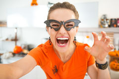 Happy young woman in Halloween decorated kitchen taking selfie Stock Images