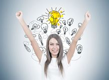 Happy young woman with hands in the air, idea. Smiling young woman with brown hair wearing a white t shirt is standing with her hands in the air and looking at Royalty Free Stock Photography