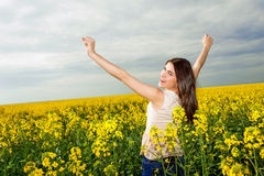 Happy young woman with hands in the air Stock Photo