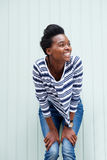 Happy young woman with hands on knees and smiling Stock Images