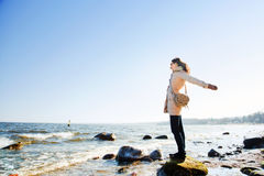 Happy young woman with hands up, sunny day on the beach. Stock Photo