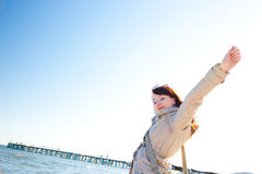 Happy young woman with hands up, sunny day. stock photo