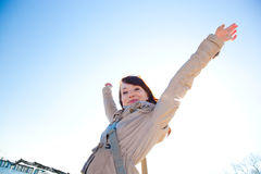 Happy young woman with hands up, sunny day. royalty free stock image