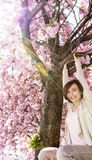 Happy young woman is hanging on the sakura tree with reflected s Stock Photo