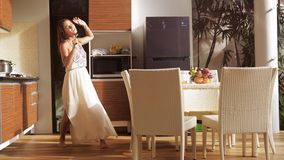 Happy young woman has fun singing and dancing in the kitchen while making breakfast in sunny morning. 3840x2160 stock footage