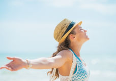 Happy young woman in hat and with bag rejoicing on beach Royalty Free Stock Photo