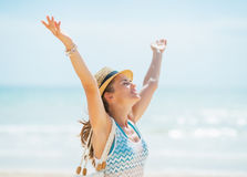 Happy young woman in hat and with bag rejoicing on beach Royalty Free Stock Image