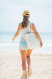 Happy young woman in hat and with bag running on beach Royalty Free Stock Images