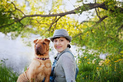 Happy young woman in a hat with dog Shar Pei sitting in the field in sunset light, true friends forever Stock Photography