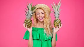 Young woman in hat holding a pineapple on a pink background. Happy young woman in hat holding a pineapple on a pink background stock footage