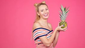 Young woman holding a pineapple on a pink background. Happy young woman in hat holding a pineapple on a pink background stock footage