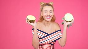 Young woman holding a pineapple on a pink background. Happy young woman in hat holding a pineapple on a pink background stock video footage