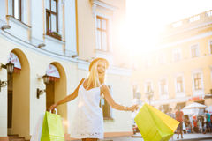 Happy young woman in hat holding shopping bags while walking. Happy young blonde woman in hat holding shopping bags while walking on the street royalty free stock image