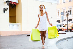 Happy young woman in hat holding shopping bags while walking. Happy young blonde woman in hat holding shopping bags while walking on the street Royalty Free Stock Images