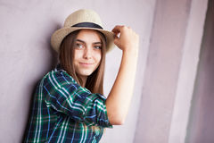 Happy young woman in hat near pink wall. Beautiful young woman in hat posing near pink wall Stock Photos