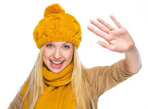 Happy young woman in hat and scarf greeting Royalty Free Stock Image