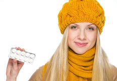 Happy young woman in hat and scarf showing pack of pills Royalty Free Stock Photos