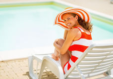 Happy young woman in hat sitting on sunbed Royalty Free Stock Image