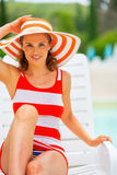 Happy young woman in hat sitting on sunbed Royalty Free Stock Photography