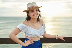 Happy young woman in hat. On sunset light ocean background Royalty Free Stock Image