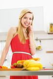 Happy young woman having a bite while cutting salad. In modern kitchen Royalty Free Stock Photo