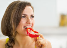 Happy young woman having a bite of red bell pepper Stock Images