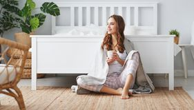 Happy young woman having coffee in morning in bed stock photos
