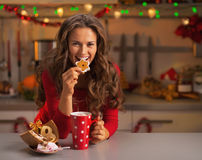 Happy young woman having eating christmas cookies in kitchen Royalty Free Stock Images