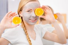 Happy young woman having face mask holding kiwi Royalty Free Stock Photo