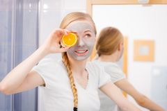 Happy young woman having face mask holding kiwi Stock Image