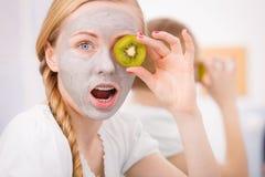 Happy young woman having face mask holding kiwi Stock Photo
