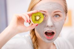 Happy young woman having face mask holding kiwi. Facial dry skin and body care, complexion treatment at home concept. Happy young woman having grey mud mask on Stock Photo
