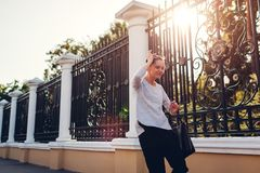 Happy young woman having fun in summer park. Girl imitates wavy walk with her body and smiles royalty free stock photo
