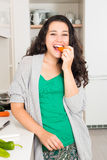Happy young woman having a healthy snack while cooking Stock Photo