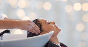 Happy young woman having salon hair wash stock photo